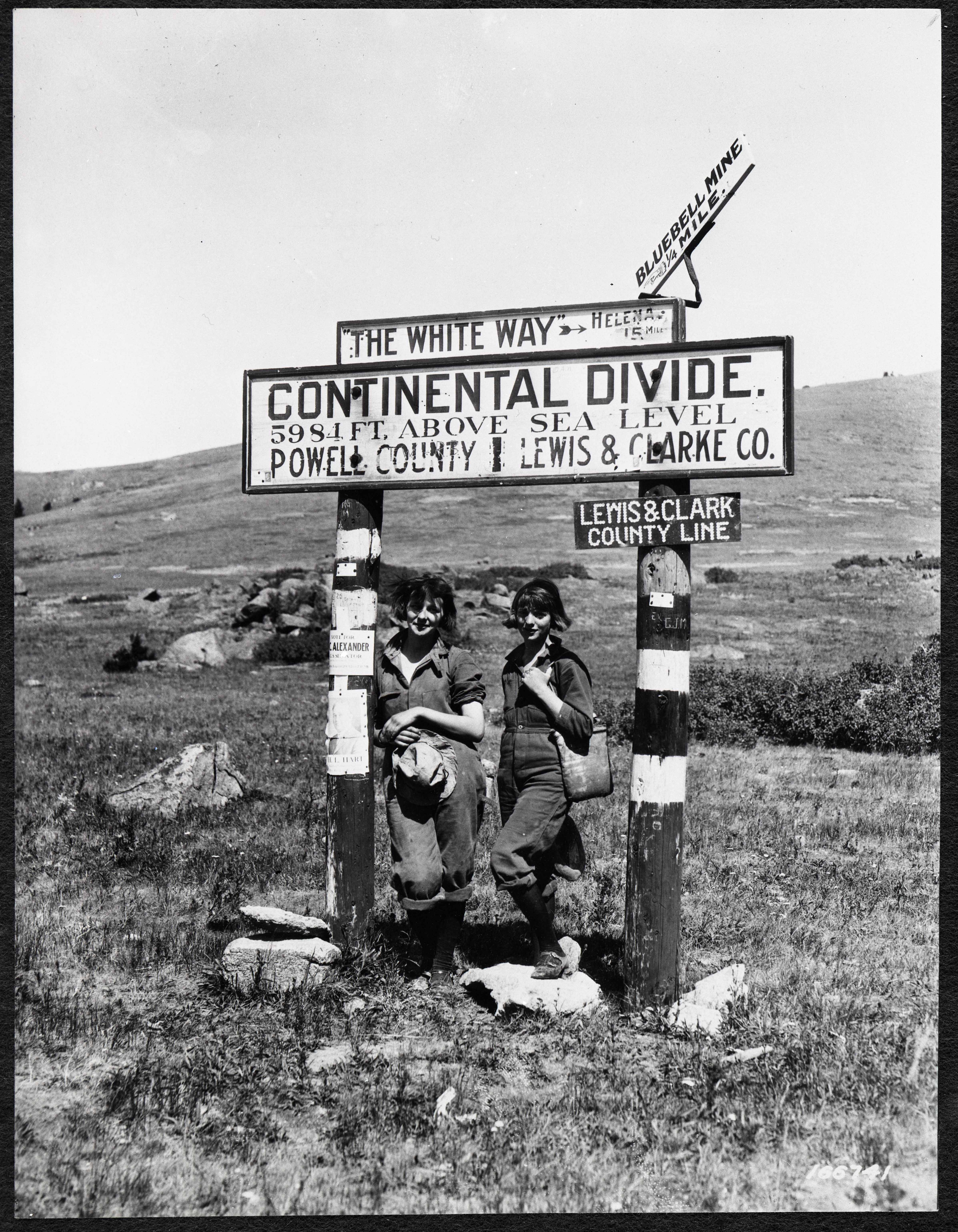 Two women standing beneath a sign