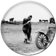 Young Native American woman with young child strapped to her back and 1920s model car in foreground