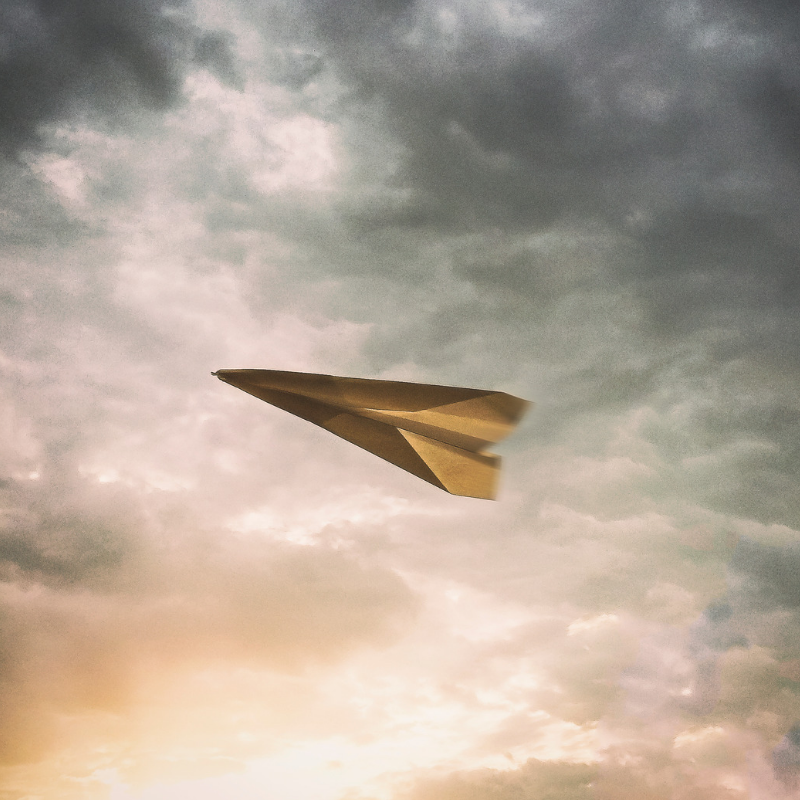 Paper airplane aflight in a cloudy sky