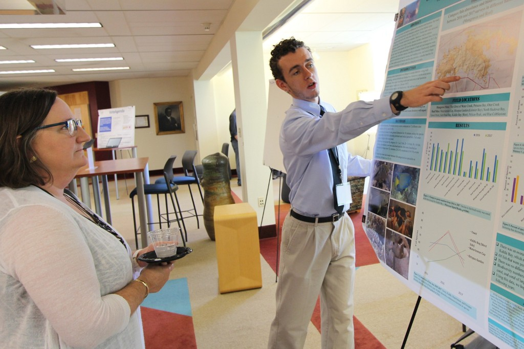 Student pointing at poster while professor watches