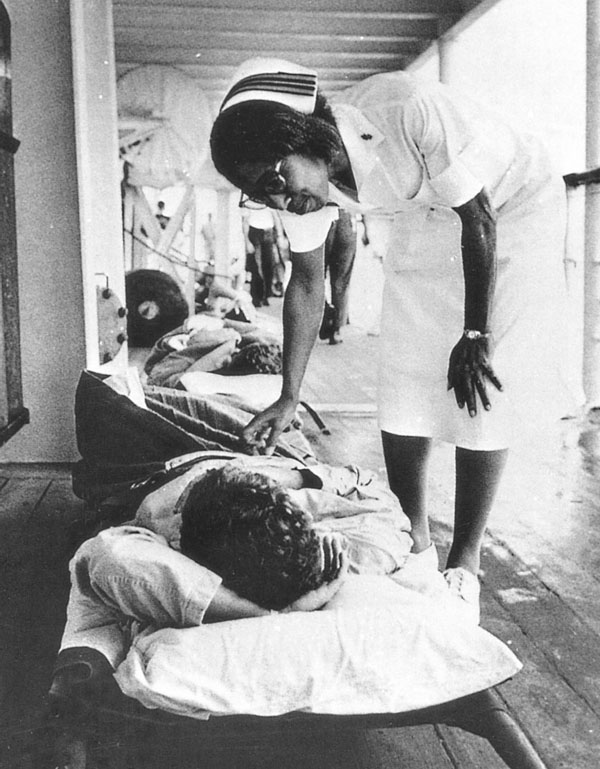 A U.S. Navy nurse provides a comforting touch and kind word to a wounded man on board the hospital ship Repose off Vietnam, 1967.