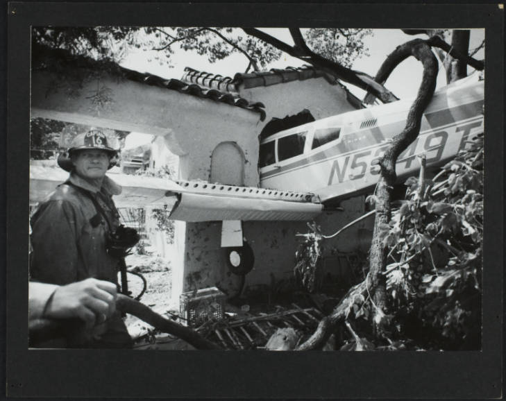 airplane crashed into home with fireman posing in front