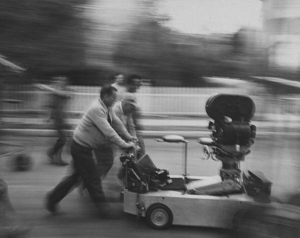 Film crew moving a camera on a backlot, March 1960