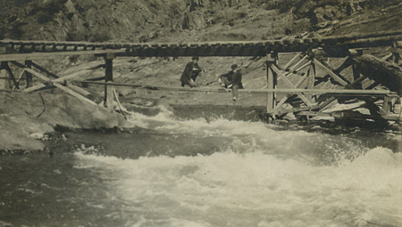 Two men on makeshift bridge over river, undated.  June English Forestry collection.