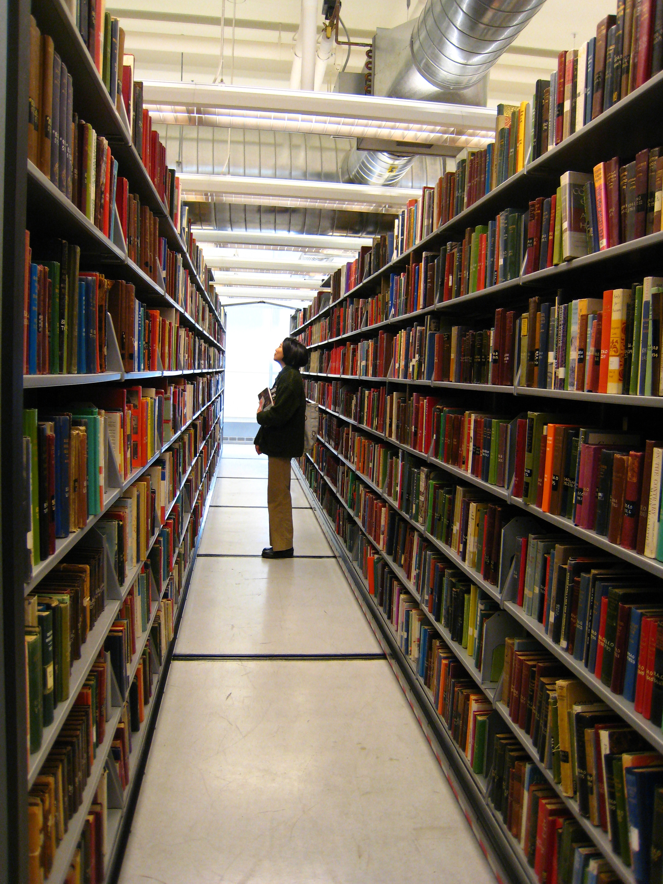 Person standing between shelves of library books