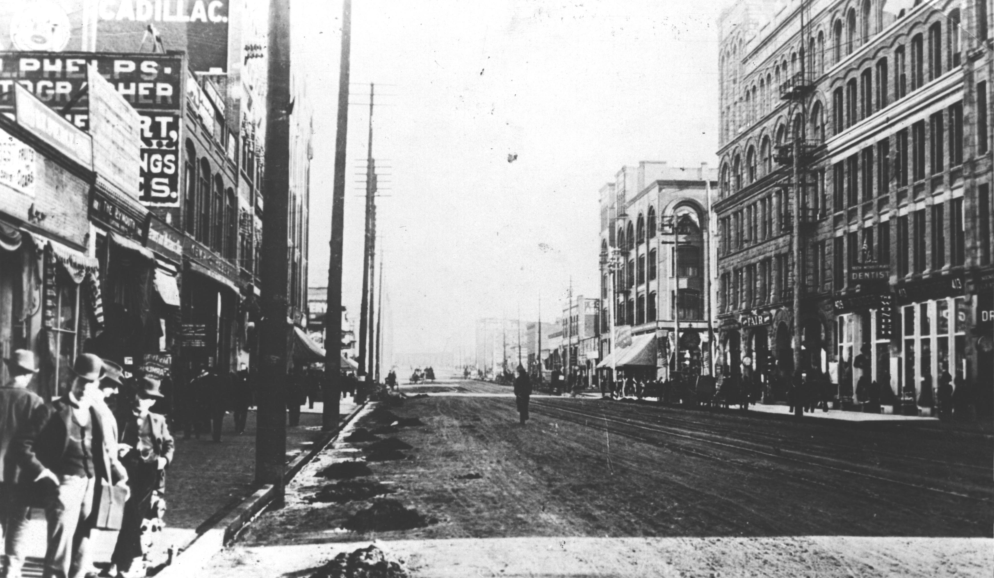 Historic Downtown, 1895-1900. A view down the center of the street with a few men in the lower left corner in historic clothes.