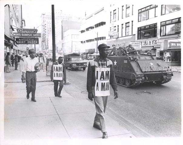 "Strikers wearing signs that read ""I AM A MAN"" marching down Main Street while National Guardsmen in an armored personnel carrier patrol alongside, March 1968."