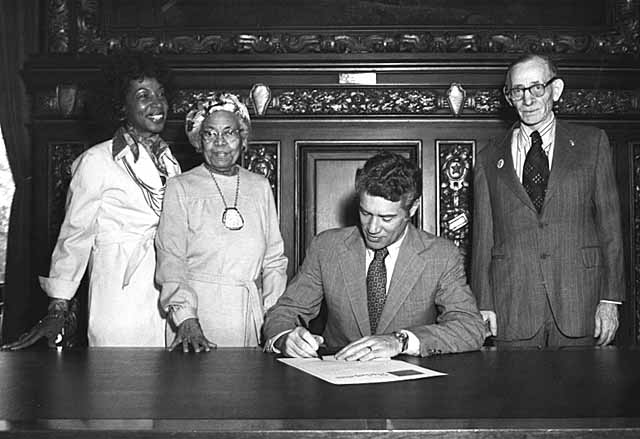 Governor Wendell Anderson signing proclamation with onlookers, ca. 1976