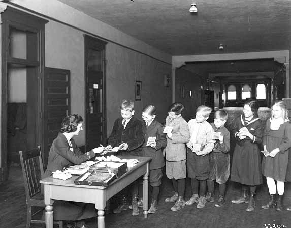 Group of children at Harriet School depositing money in their savings accounts, photograph used as part of an advertising campaign by Farmers & Mechanics Savings Bank to promote savings programs for children, 1920