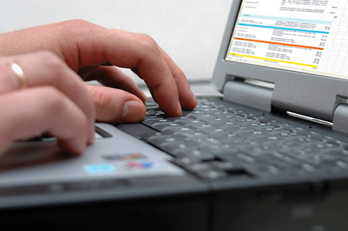 photograph of hands typing on a laptop