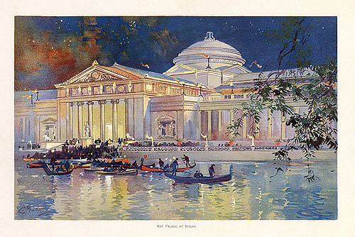 Image of a Greek revival building at night with boats on the water in front.