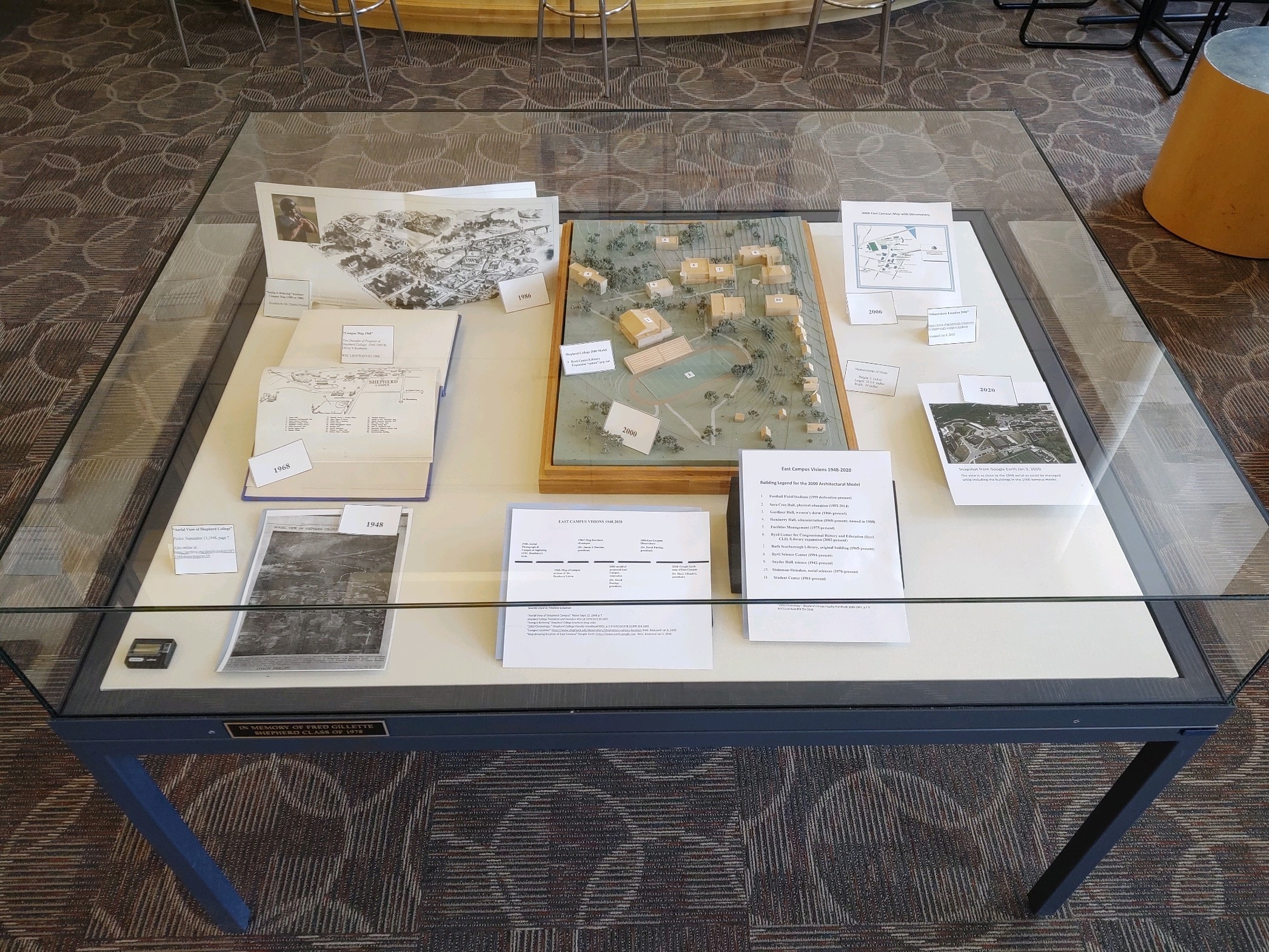 Display titled East Campus Visions 1948-2020, including an architectural model from 2000, several campus maps, an aerial photograph, and a Google Earth snapshot