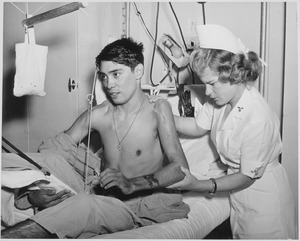 Young soldier (WW-2) receiving physical therapy from a nurse
