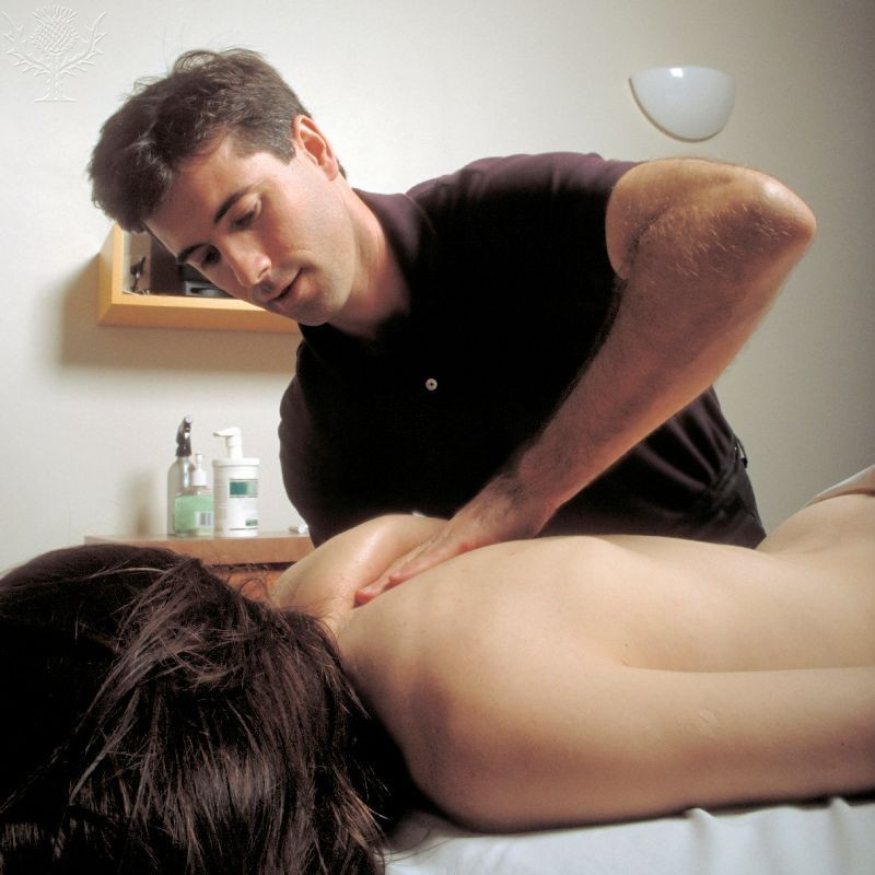 Massage therapist working on a patients shoulder