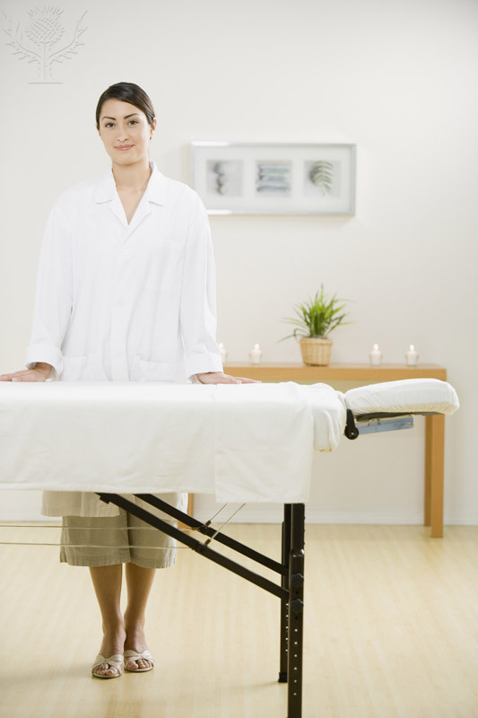 Massage therapist standing behind a massage table