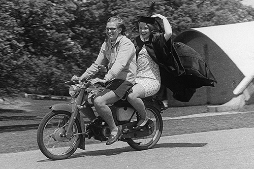 A student gets a ride on a moped after the commencement ceremony.