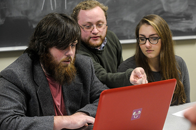 Professor and 2 students with computer