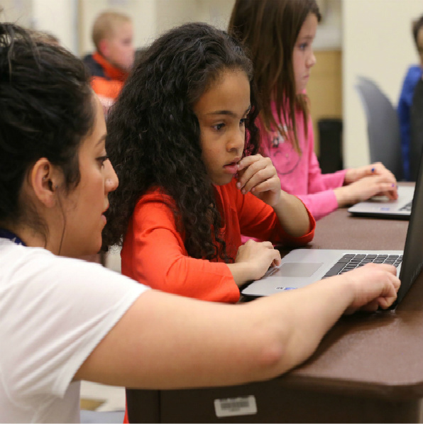image of a librarian teaching a coding course with a little girl