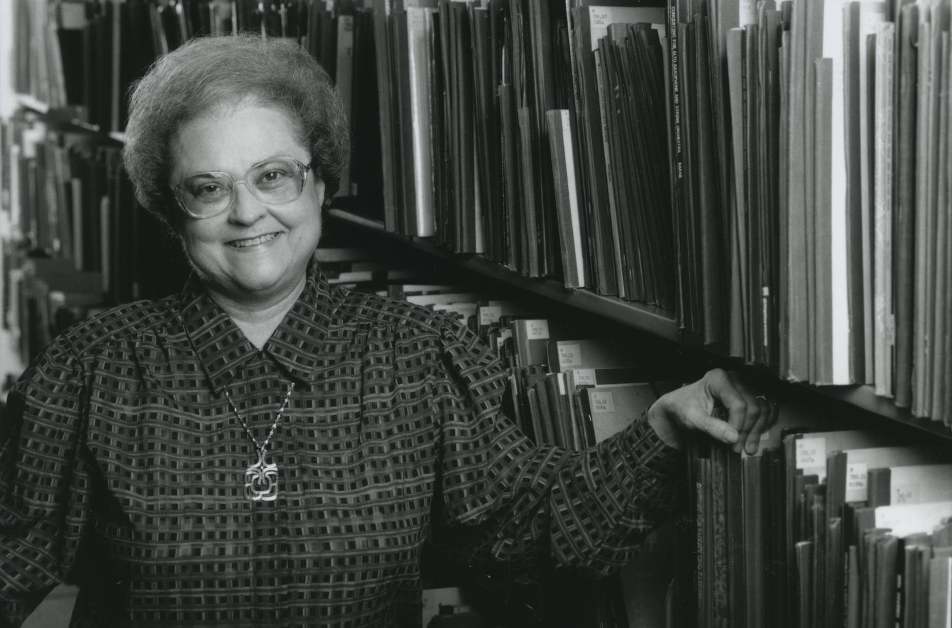 Black and white photograph of Shirley Marie Watts standing in front of shelves filled with music scores.
