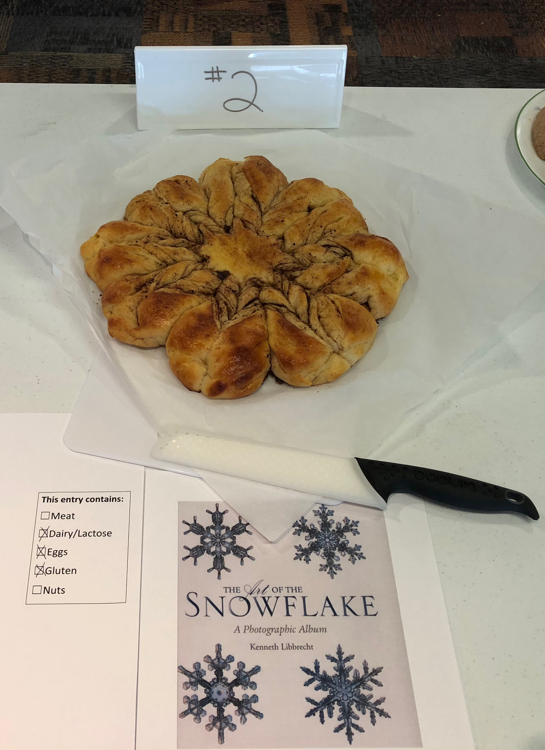 An intricately braided loaf of bread arranged to look like a snowflake, with swirls of cinnamon, cocoa, and sugar.