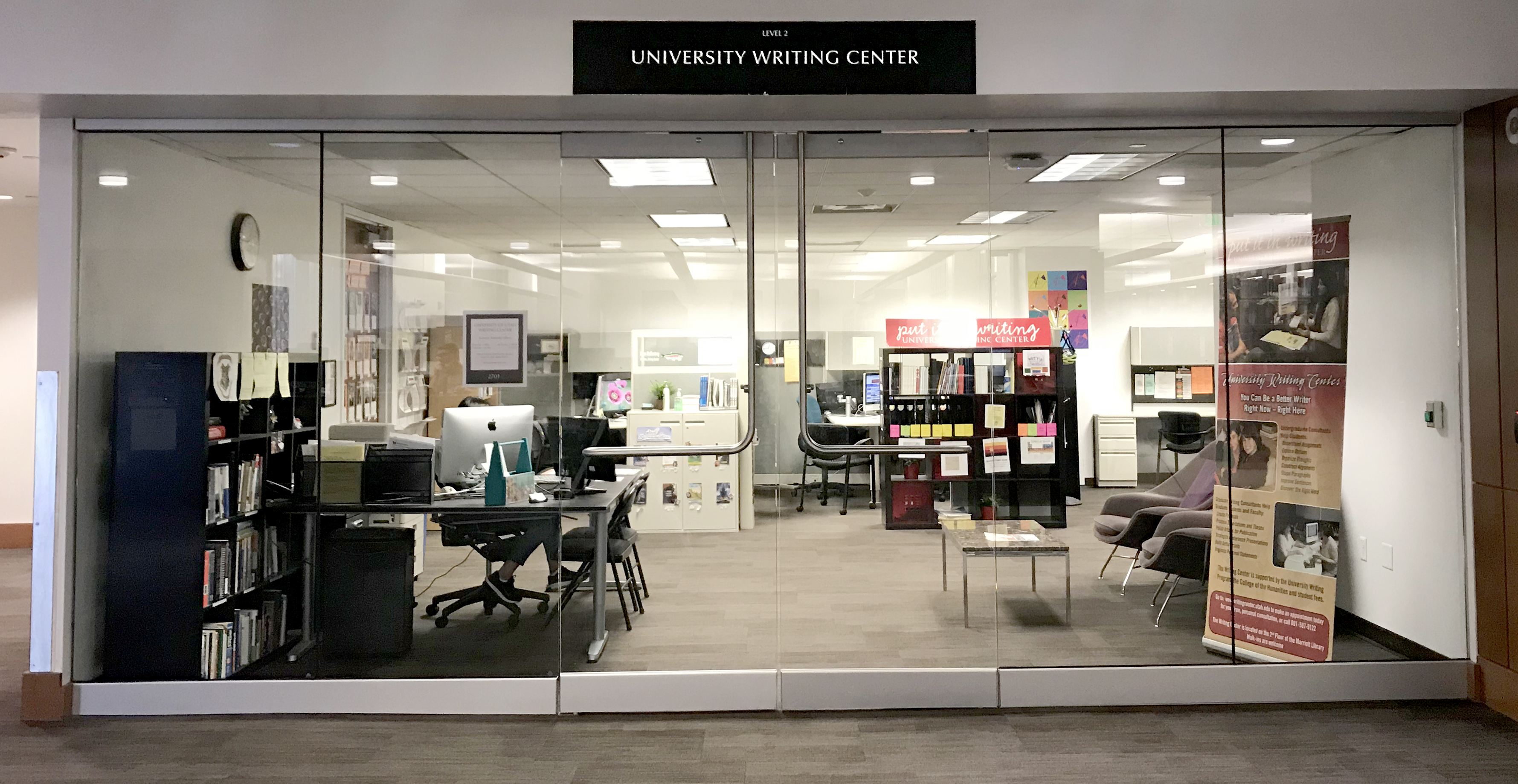 "An office behind glass doors.  There are sectioned cubicles for writing consultations behind a front desk area with an iMac computer.  Above the doors is a sign that reads ""University Writing Center."""