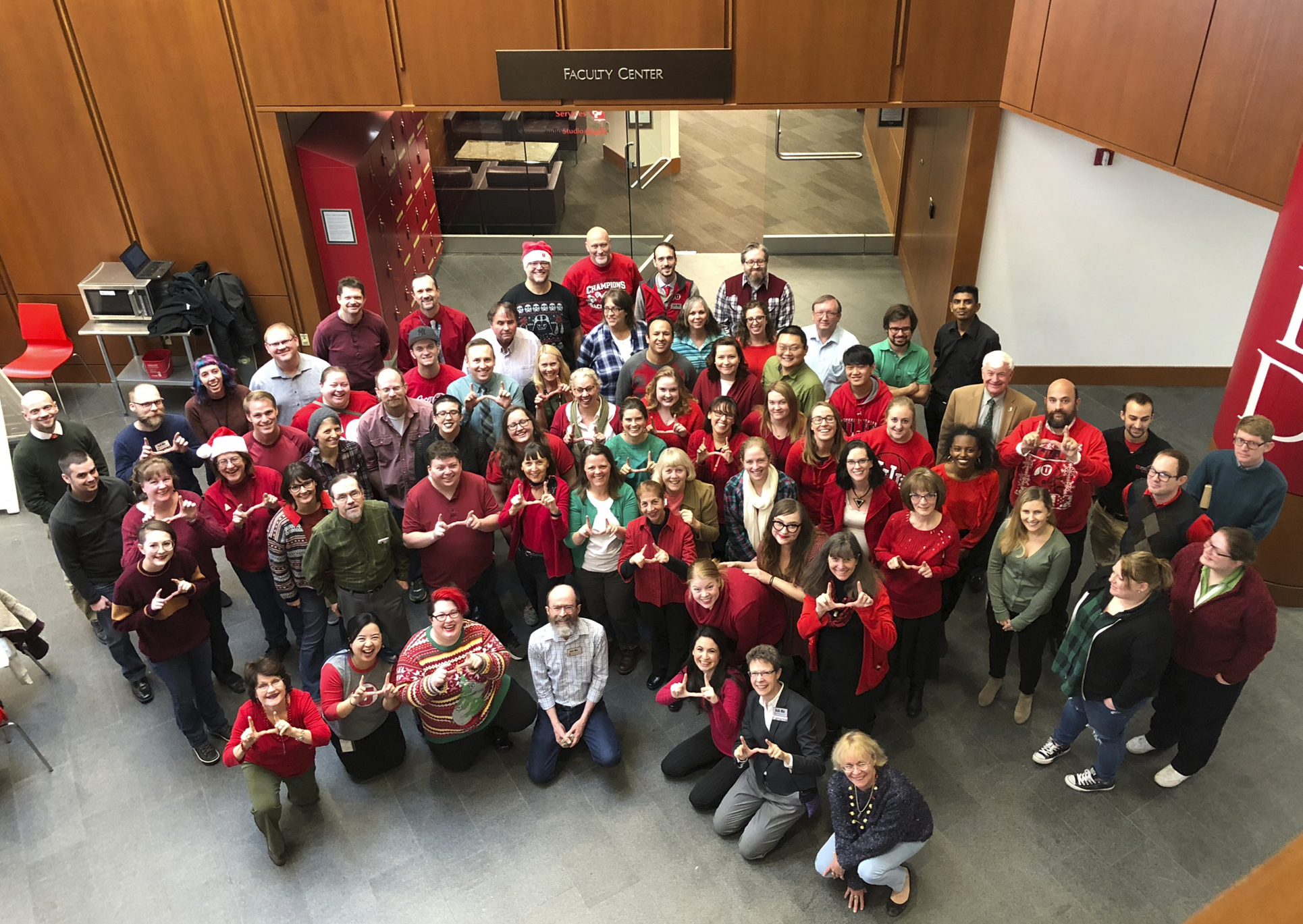 group of librarians and staff from the Marriott Library in holiday themed clothing.  Many of them are making a U with their hands.