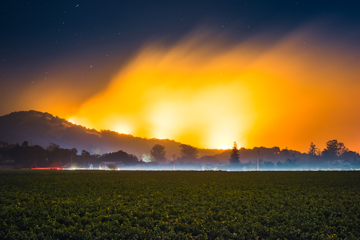 fire's glow in the sky behind hills
