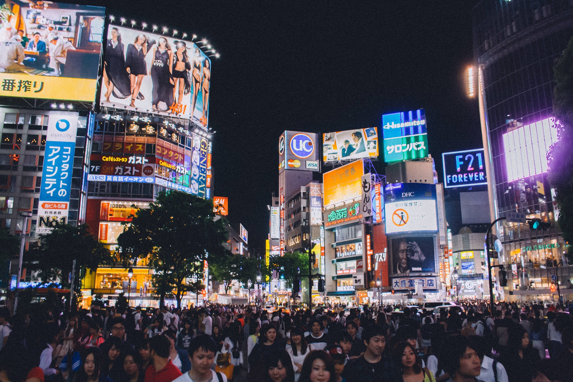 photo of crowded shibuya crossing at night with advertisements