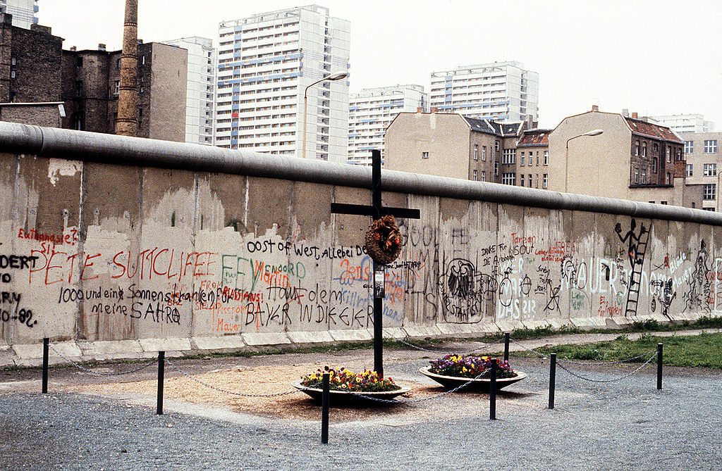 The Berlin Wall with a cross and small memorial