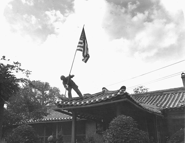 U.S. Marine raises flag in Seoul.