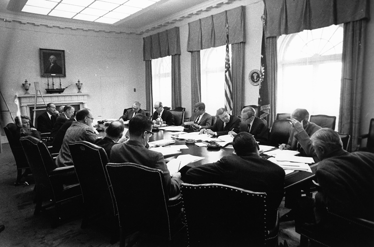 Government officials crowded around a table with President Kennedy in the middle
