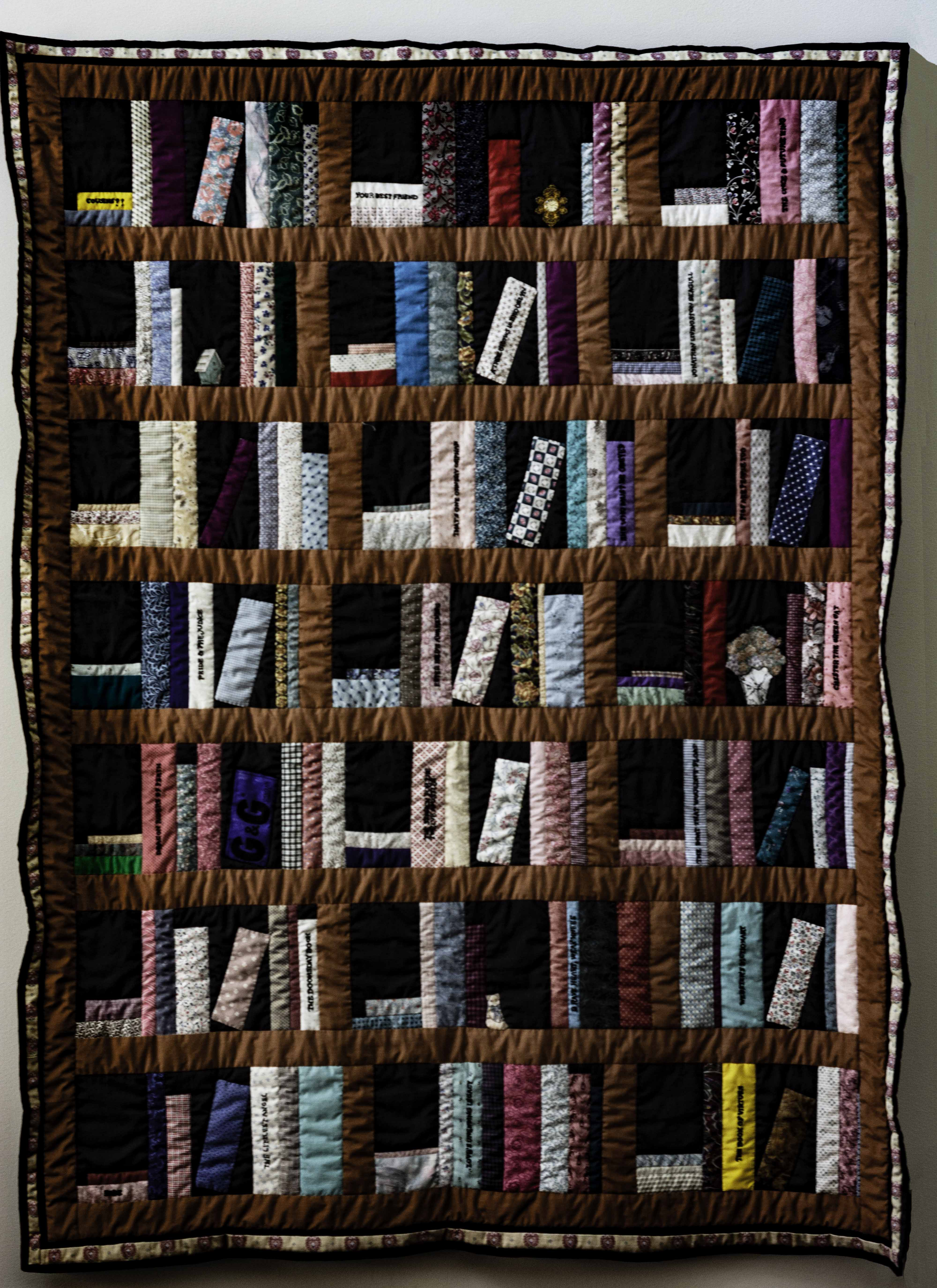 quilt depicting bookshelves with titles on spines