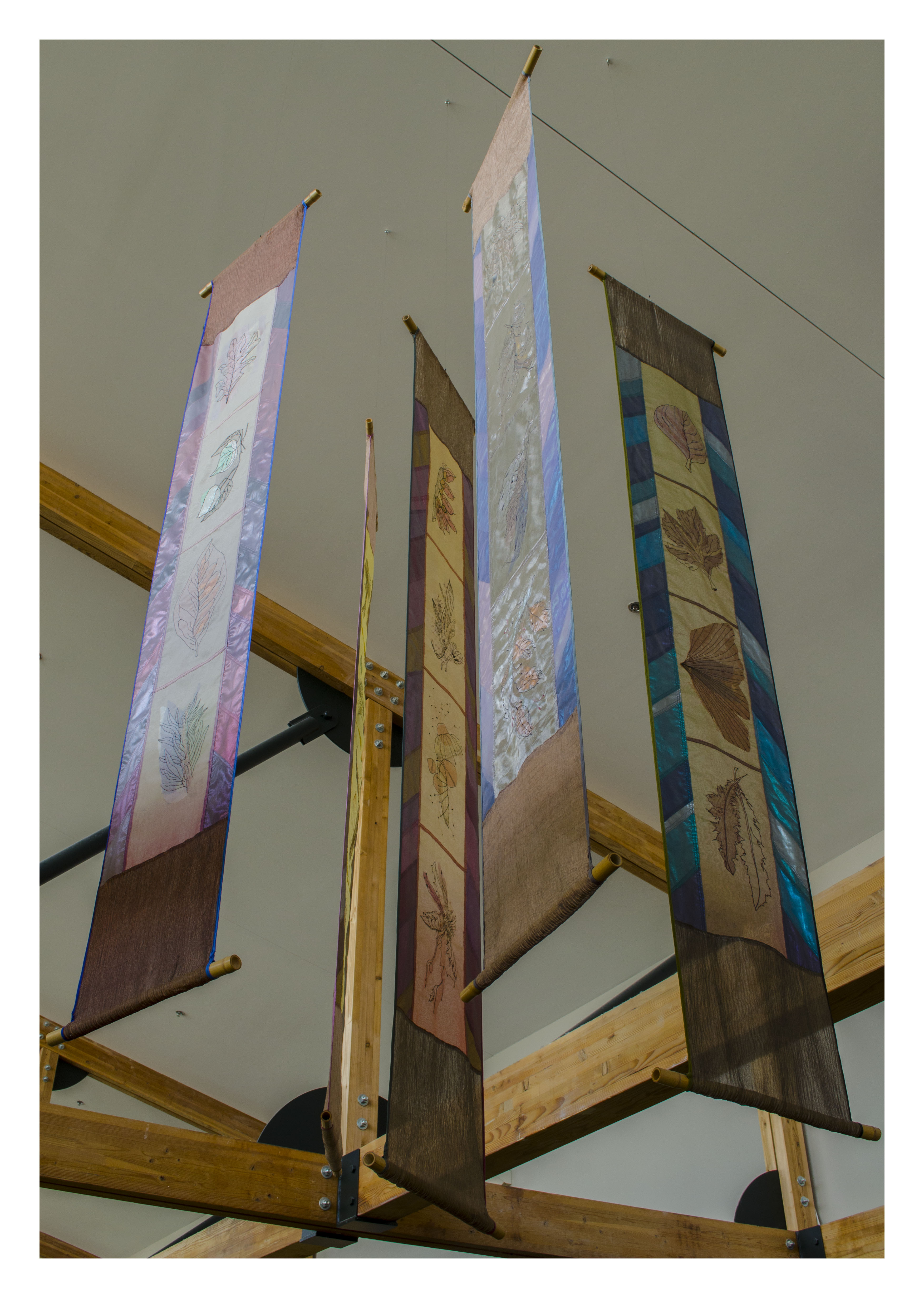 hanging banners with leaf imprints on squares of colorful silk