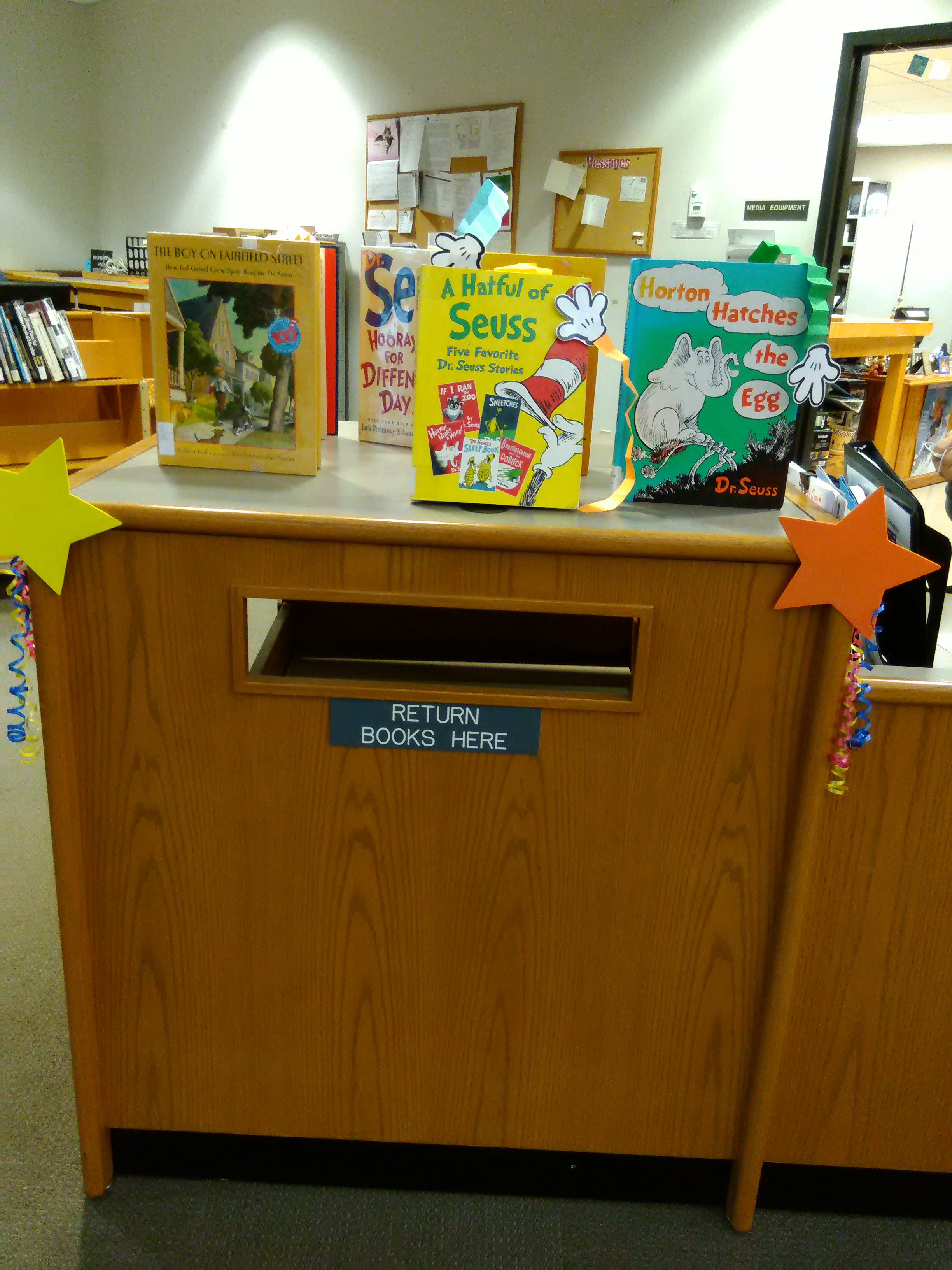 Display of Dr. Seuss books from our collection with colorful  accordion style hands popping out of the books