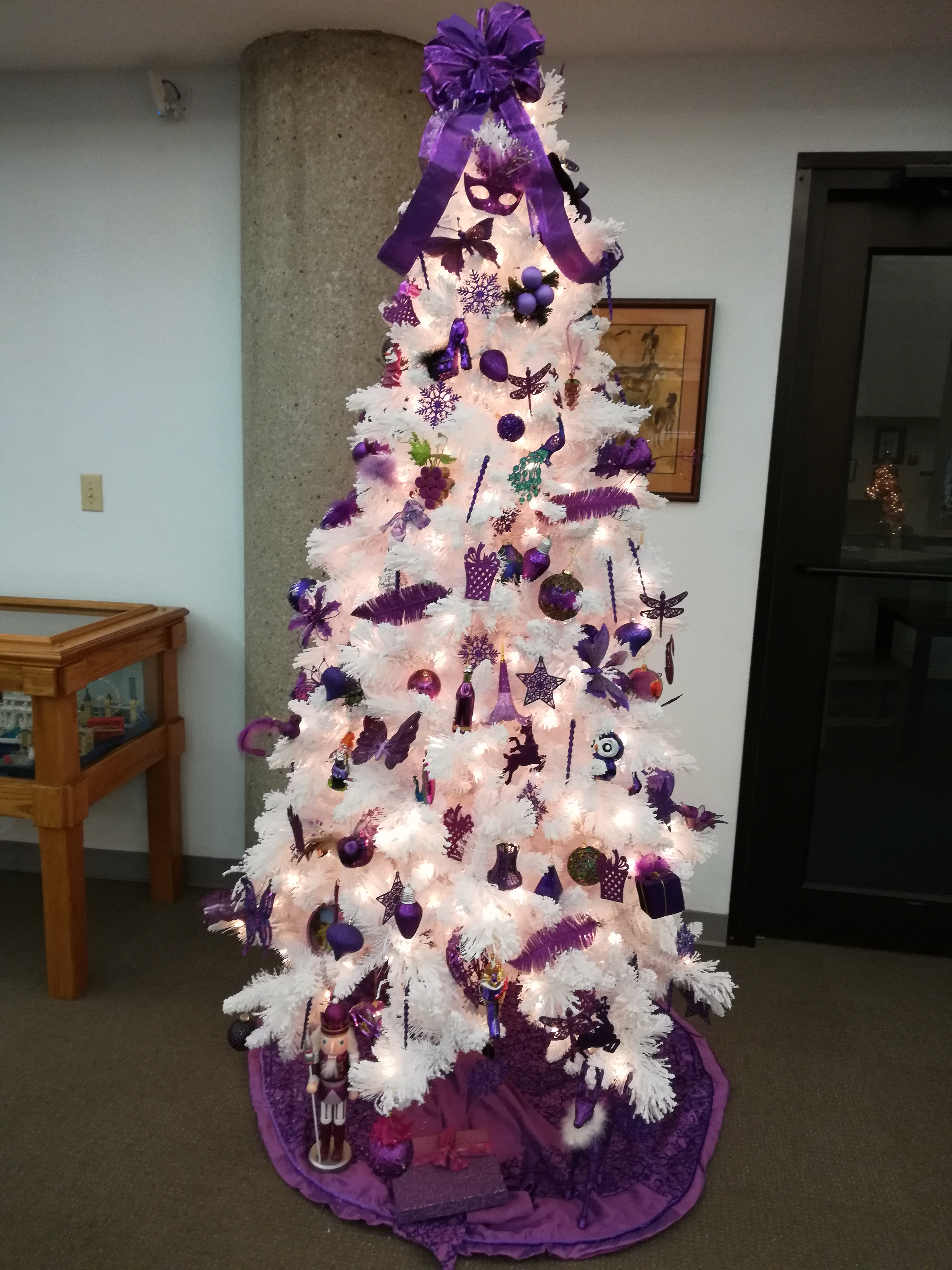 White frosted Christmas tree with purple decorations outside the inter-library loan office