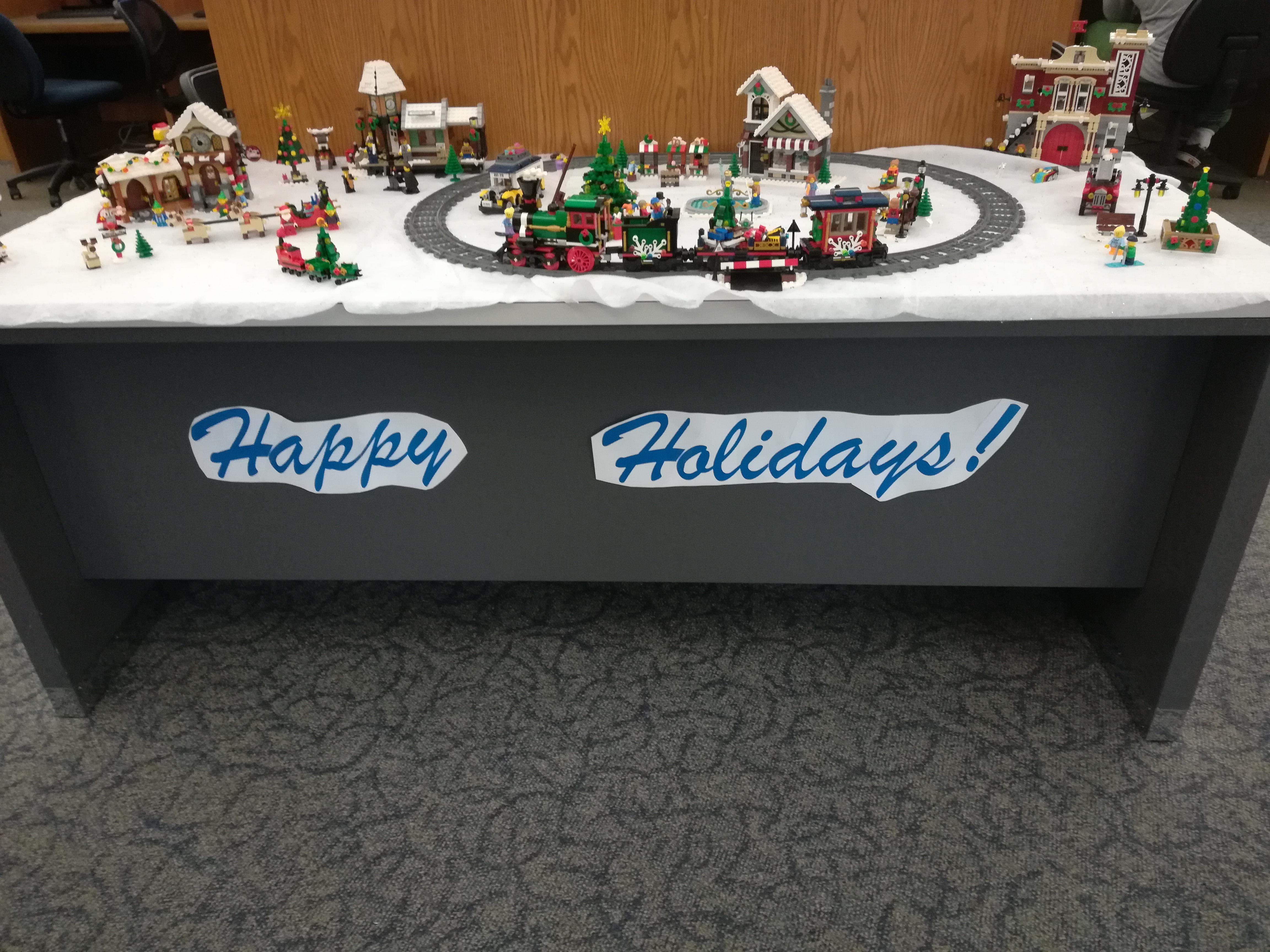 "Lego Christmas Village with an operational train and a sign that reads"" Happy Holidays"""
