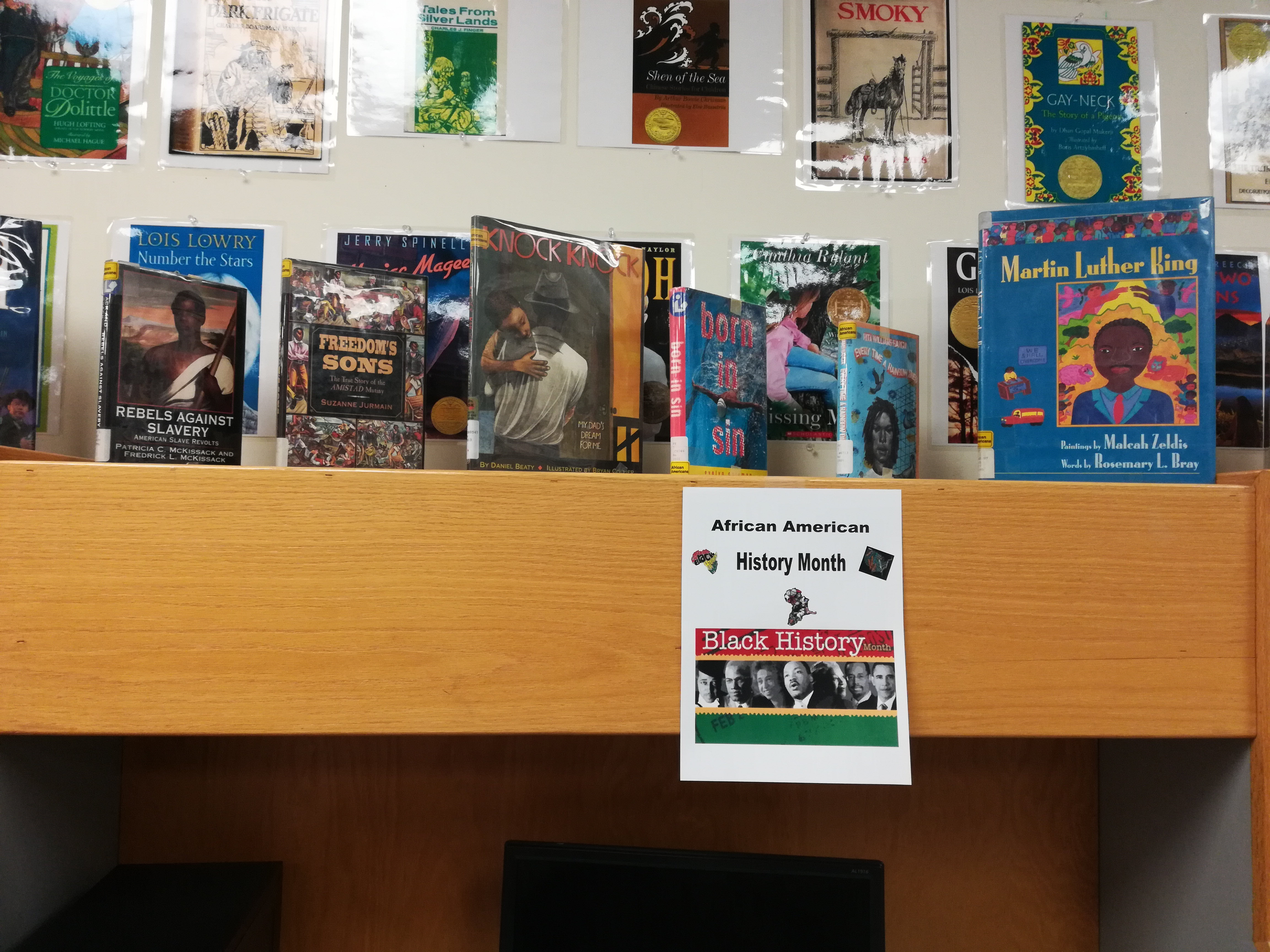 Books on display for Black History month in the curriculum room of the library, Decorative printed sign that say African American History Month