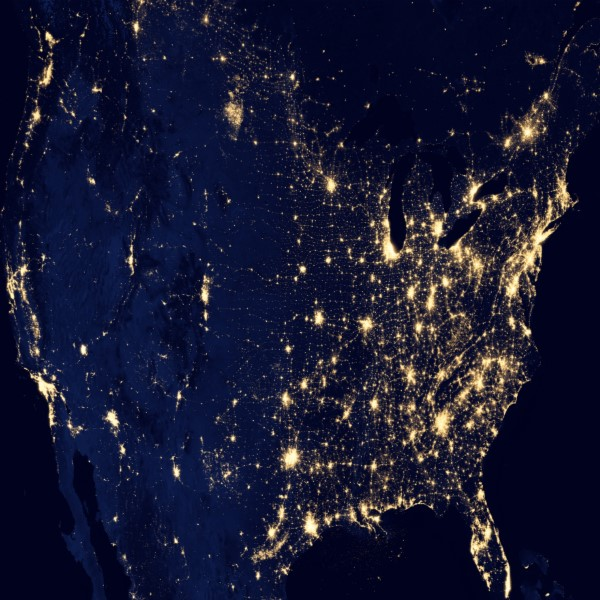 a satelite view of the united states at night. you can see the major cities by where the lights are concentrated.