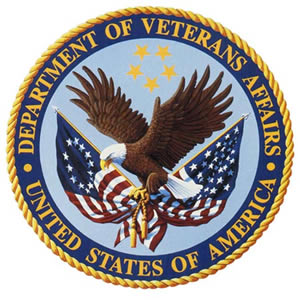 A circular medalion with the VA logo surrounded by the agency name. The logo is an eagle clutching the original american flag and the modern american flag in its talons.