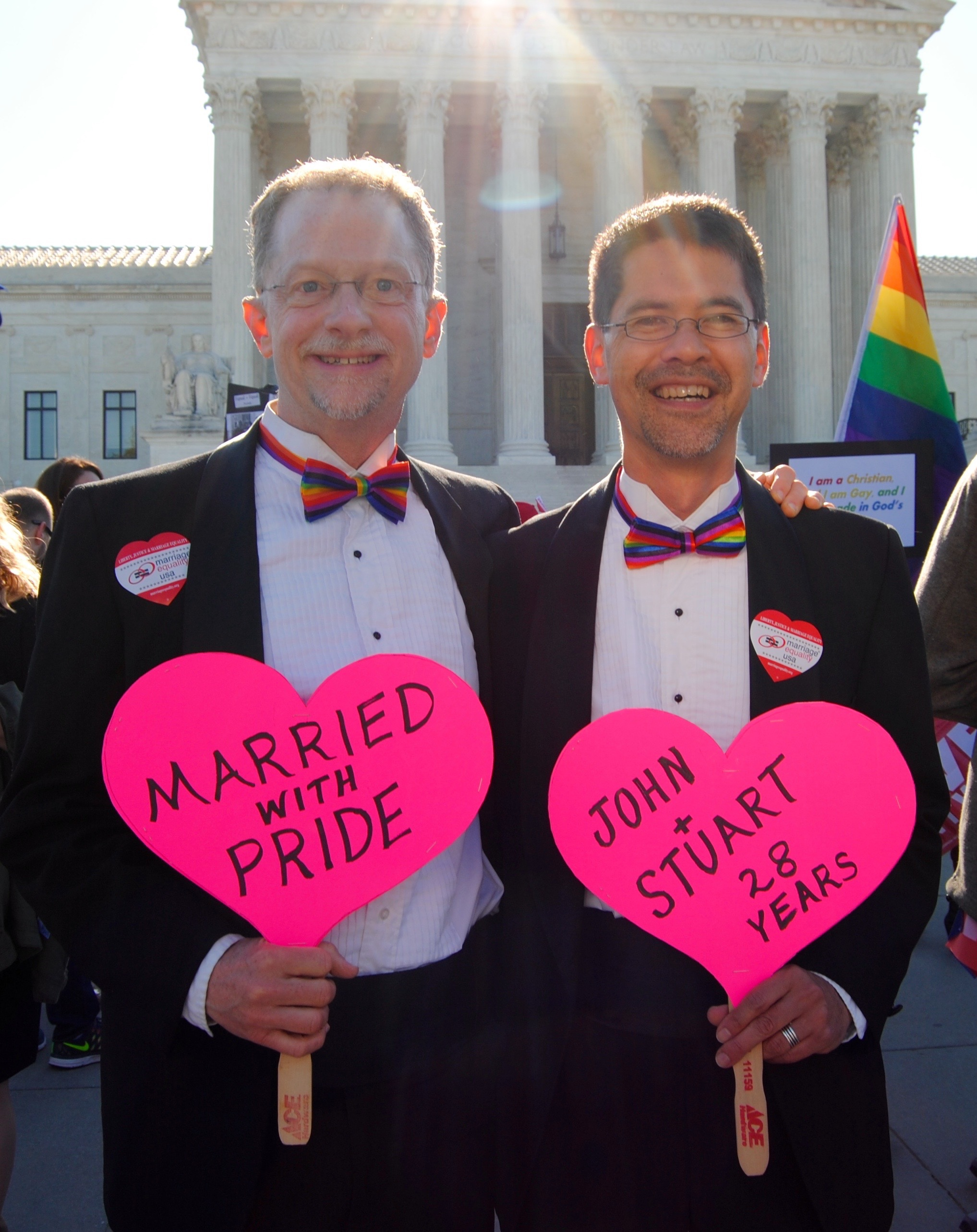 A gay couple protest in front of the Supreme Court