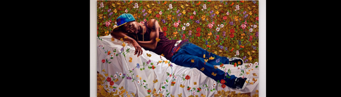 Portrait of young man in baseball cap resting on a bed, surrounded by a wall and sheet with decorative flowers, by artist Kehinde Wiley