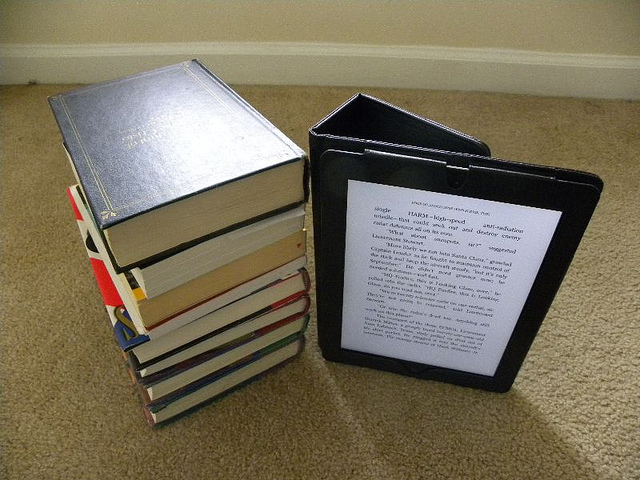 A stack of print books and an ebook reader