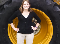 Lydia in front of a large tractor tire