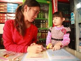 A mother helps her daughter with homework in Kunming.