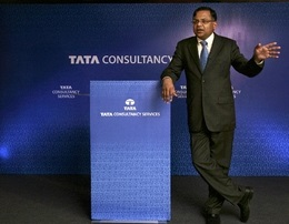 Man speaking in front of podium; outsourcing company Tata Consultancy sign in the background.