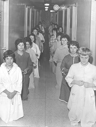 Taken in the early 1960's, this photo shows students lined up in a Corona hallway praying the rosary at bedtime.