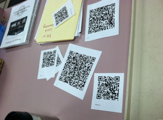 bulletin board with qr codes pinned to it
