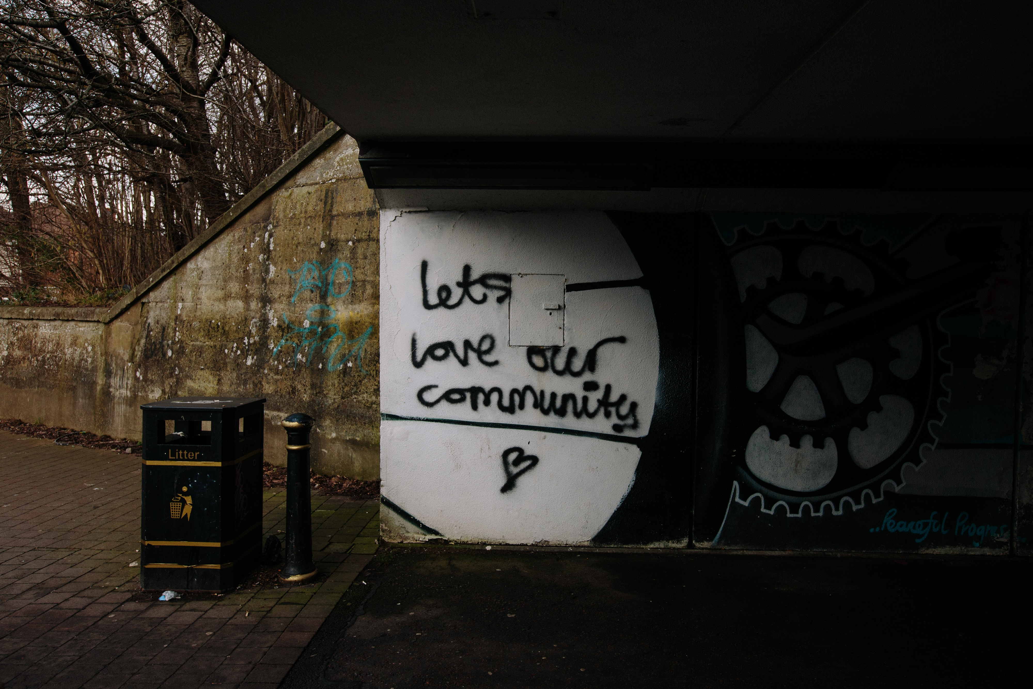 image is of graffiti under a bridge that says lets love our community
