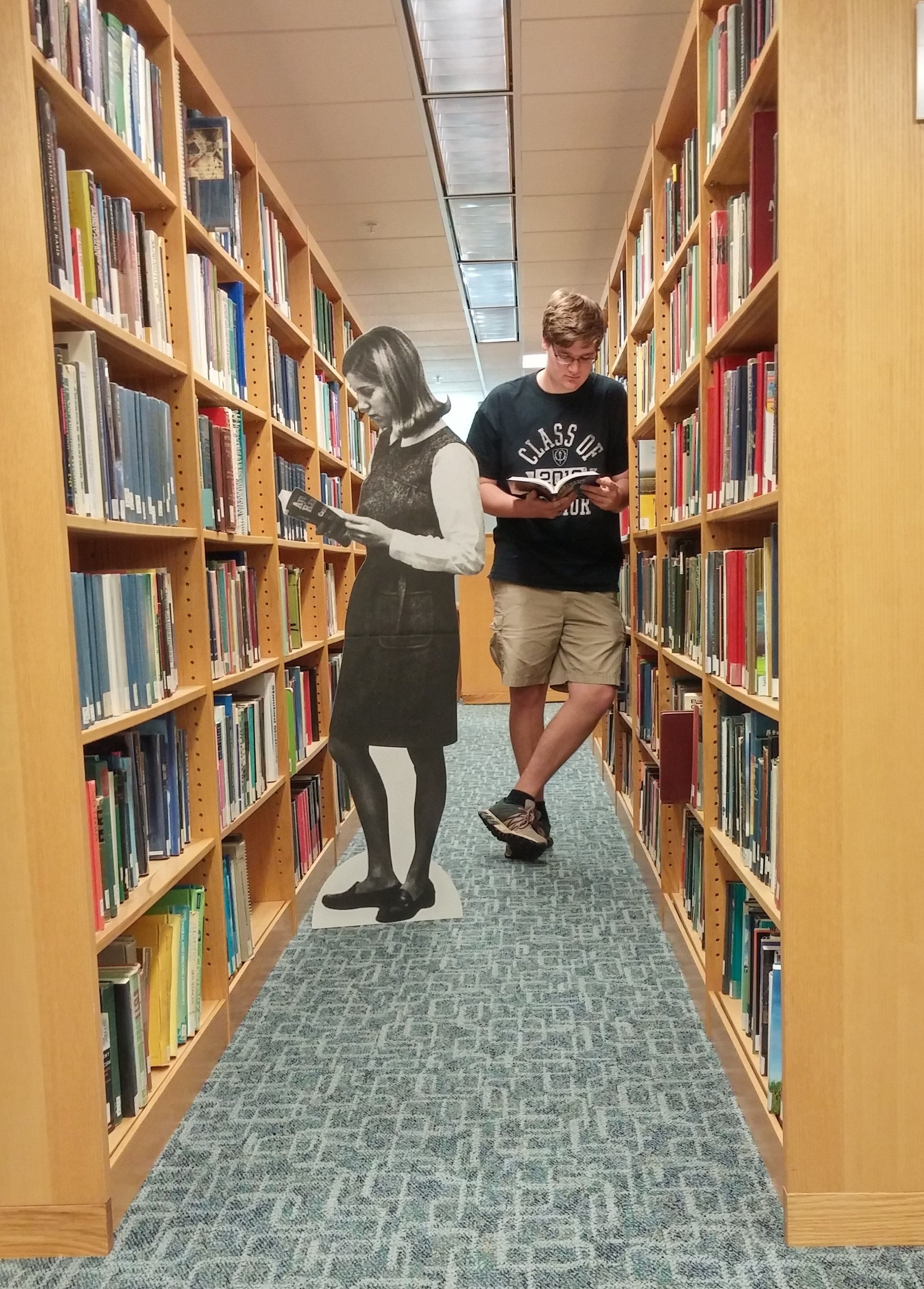 Student between rows of books in library