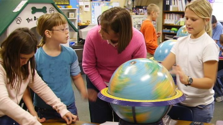 Photograph of a female adult in a classroom with a group of children standing around a globe.